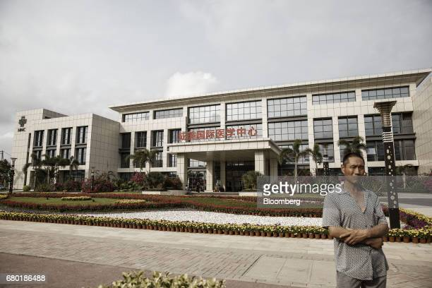 A man stands near a newly built hospital inside the Hainan Boao Lecheng InternationalMedicalTourismPilotZone in Boao China on Saturday March 25...