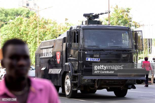 A man stands near a police water cannon as police disperse supporters of the former Senegalese president gathered for an unauthorised rally on...