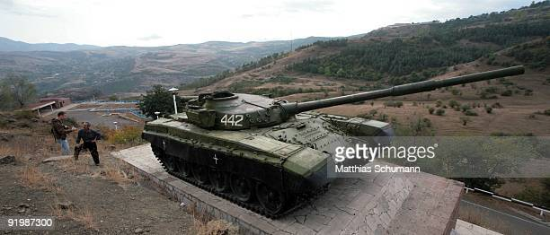 A man stands near a restored T72 tank which stands as a memorial commemorating for the capture of the town Shusha beside the street between...