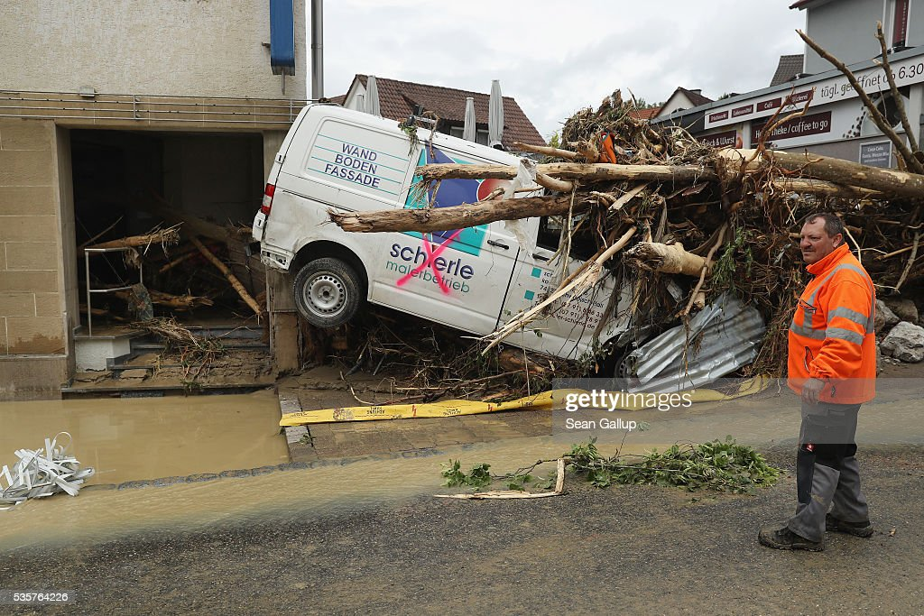 A man stands near a smashed car, trees and storefront in the village center following a furious flash flood the night before on May 30, 2016 in Braunsbach, Germany. The flood tore through Braunsbach, crushing cars, ripping corners of houses and flooding homes during a storm that hit southwestern Germany. Miraculously no one in Braunsbach was killed, though three people died as a result of the storm in other parts of the country.