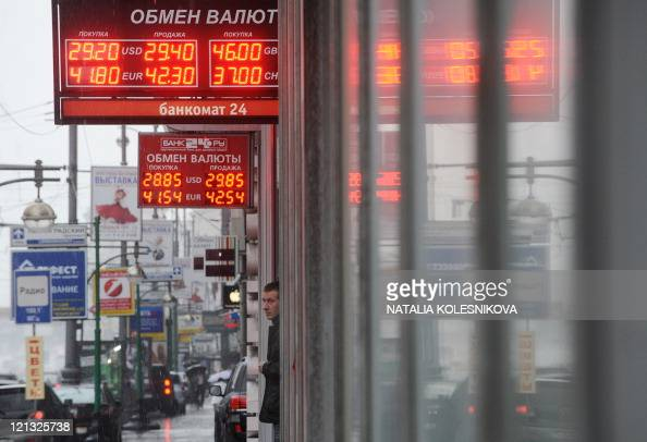 A man stands near displays of a currency exchange bureau in Moscow on August 10 2011 as Russia's two main markets opened with gains of about two...