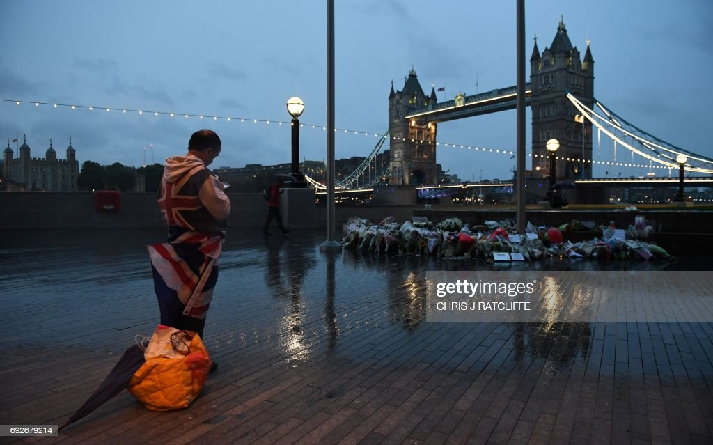 TOPSHOT - A man stands near flowers layed at Potters Fields Park in London on June 5, 2017, after a vigil to commemorate the victims of the terror attack on London Bridge and at Borough Market that killed seven people on June 3. London police made a fresh round of arrests on June 5 after the country's third terror attack in less than three months as Prime Minister Theresa May came under mounting pressure over security three days ahead of elections. The aftermath of June 3 night's rampage, which left seven dead and dozens wounded, dominated the campaign trail. PHOTO / Chris J Ratcliffe