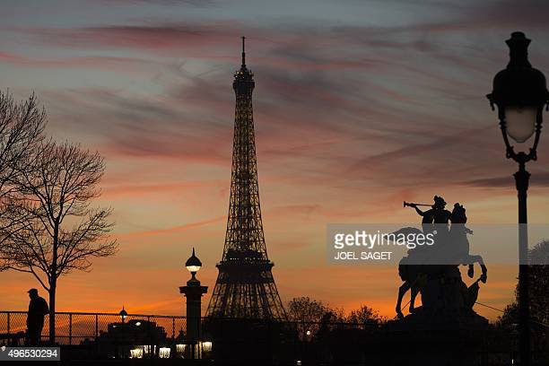 A man stands near the Eiffel tower in Paris on November 10 2015 AFP PHOTO / JOEL SAGET
