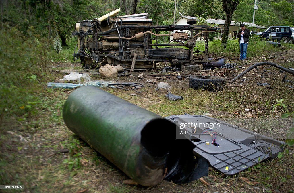 A man stands near the remains of a car bomb in El Palo, department of Cauca, Colombia, on February 5, 2013. Two car bombs were detonated allegedly by Revolutionary Armed Forces of Colombia (FARC) guerrillas at a military checkpoint in southwestern Colombia Tuesday, killing a civilian and a soldier, and injuring three soldiers.