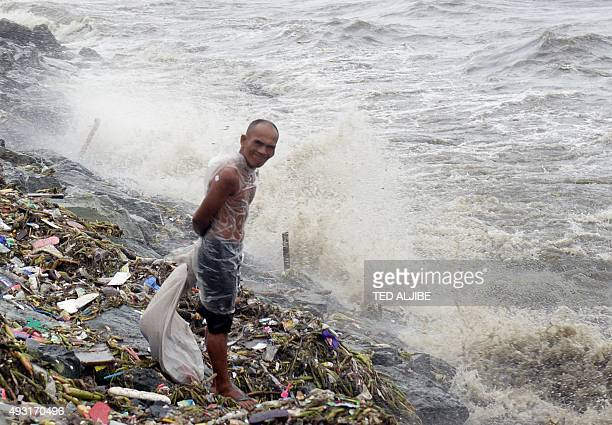 A man stands near the shore in wind and rain brought on by typhoon Koppu along Roxas boulevard in Manila on October 18 as the typhoon hit Aurora...