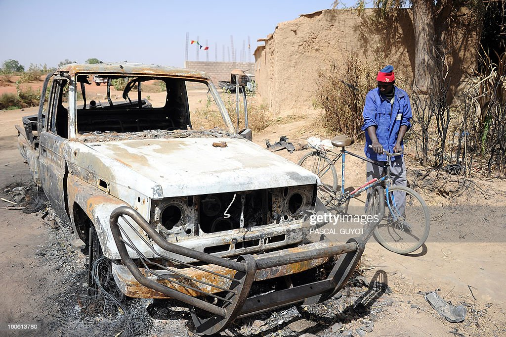 A man stands next to a bicycle past a burnt-out wreck of a vehicle, allegedly used by Islamists, following a major air strike, on February 3, 2013 in Diabaly. France said it carried out major air strikes on February 3, 2013 near Kidal, the last bastion of armed extremists chased from Mali's desert north in a lightning French-led offensive, after a whirlwind visit by President Francois Hollande. An army spokesman said 30 warplanes had bombed training and logistics centres run by Islamist extremists overnight in the Tessalit area north of Kidal, where French troops took the airport Wednesday and have been working to secure the town itself. AFP PHOTO / PASCAL GUYOT