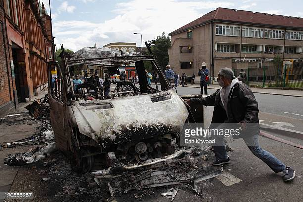 A man stands next to a burnt out van after riots on Tottenham High Road on August 7 2011 in London England Rioting broke out late last night in...