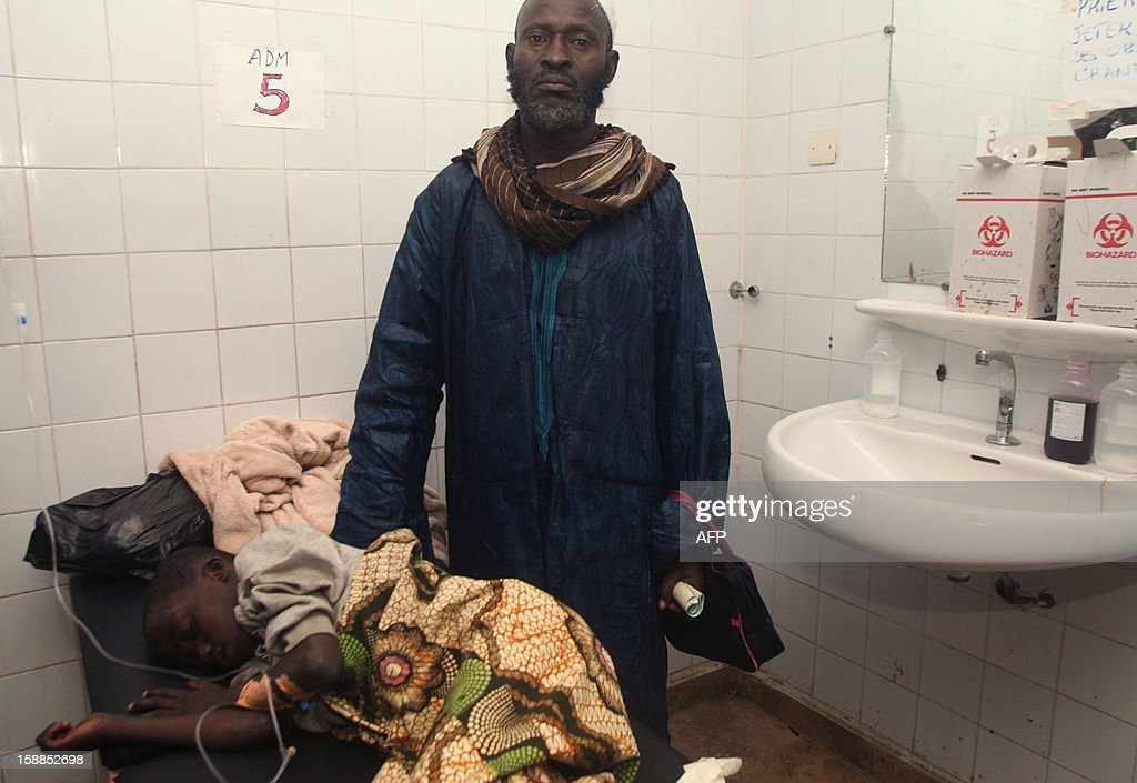 A man stands next to a child, lying on a hospital bed after he was injured in a stampede, at the Cocody hospital in Abidjan, on January 1, 2013. At least 60 people died and at least dozens were injured as crowds stampeded overnight during celebratory New Year's fireworks, Ivory Coast rescue workers said on January 1, 2013. AFP PHOTO/HERVE SEVI
