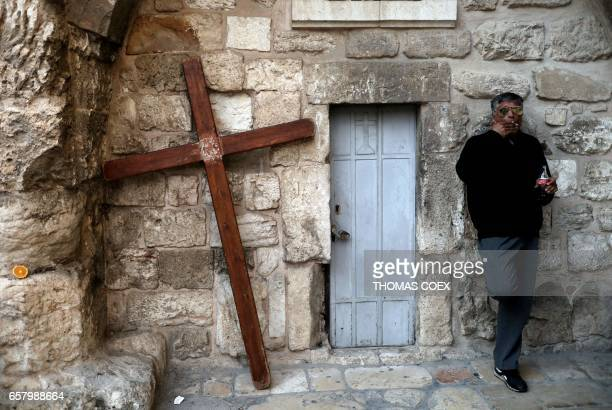TOPSHOT A man stands next to a Christian cross outside the Church of the Holy Sepulchre in Jerusalems old city on March 26 2017 / AFP PHOTO / THOMAS...