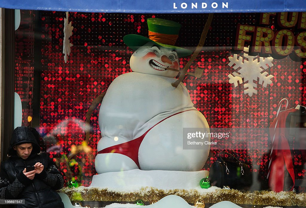A man stands next to a Christmas window display on Oxford Street on November 24, 2012 in London, England. Oxford Street was closed to traffic for its annual pedestrian only Christmas Shopping.