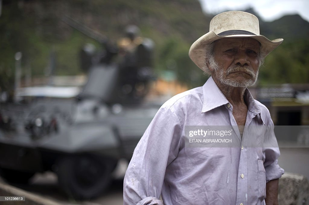 A man stands next to a Colombian army armored car along a road on the way from Bogota to Villavicencio on May 28, 2010. Colombia will hold presidential elections next May 30. AFP PHOTO/Eitan Abramovich