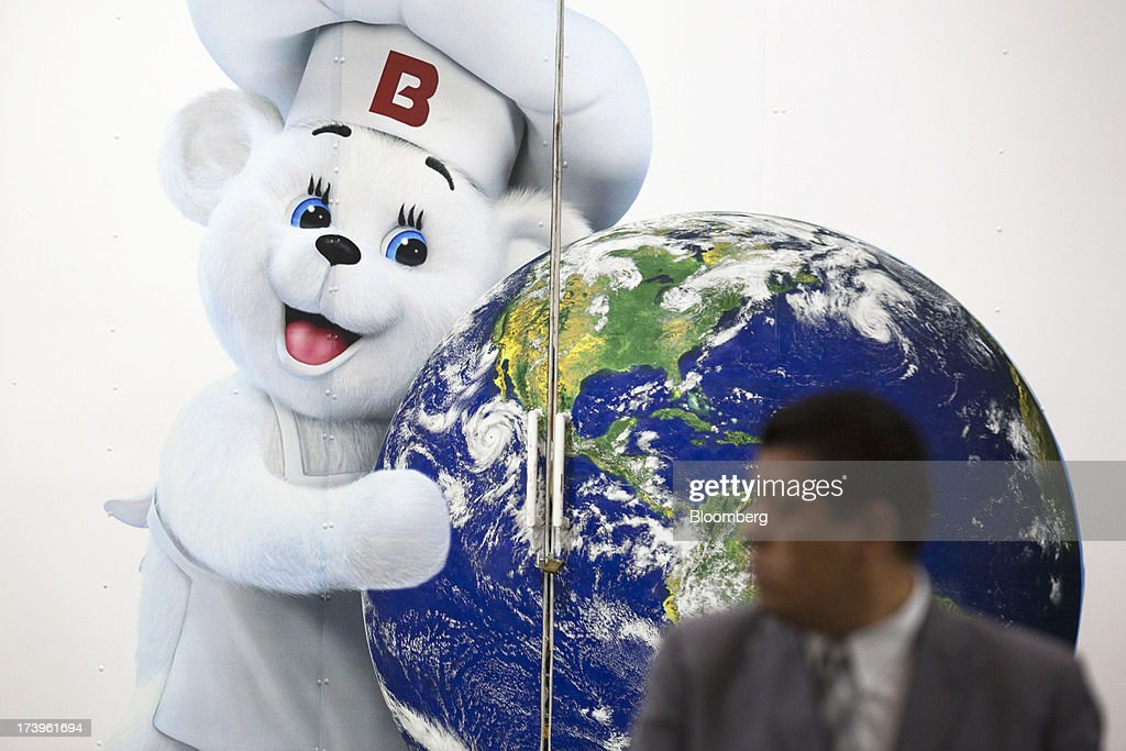 A man stands next to a photo of Grupo Bimbo SAB de CV's bear cub mascot inside the company's new sales center in Mexico City, Mexico, on Thursday, July 18, 2013. Grupo Bimbo inaugurated a new eco-friendly sales center today. Photographer: Susana Gonzalez/Bloomberg via Getty Images