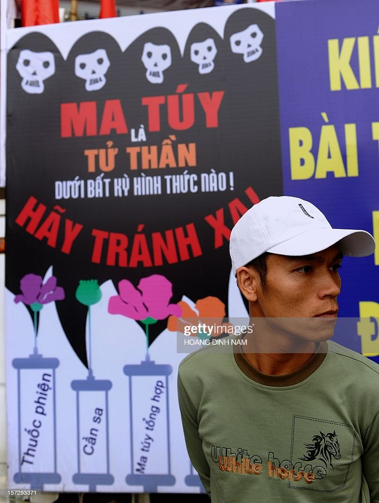 A man stands next to a poster warning that drug using is leading to HIV affection at the venue of a meeting on World's AIDS Day in Hanoi on December 1, 2012. Since the first HIV case detected in 1990, the number of cases is projected to be 280,000 or 0.47 percent of the Vietnamese population in 2012 with injecting drug users (IDU) accounting for up to 65 percent of people living with HIV. AFP PHOTO / HOANG DINH Nam