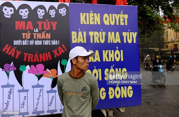 A man stands next to a poster warning that drug using is leading to HIV affection at the venue of a meeting on World's AIDS Day in Hanoi on December...