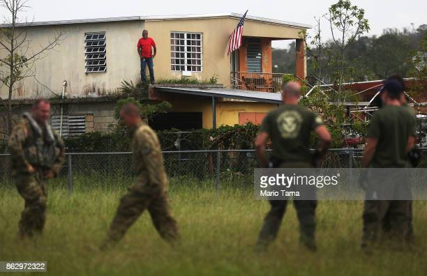A man stands next to an American flag displayed on a home during food and water delivery efforts four weeks after Hurricane Maria struck on October...