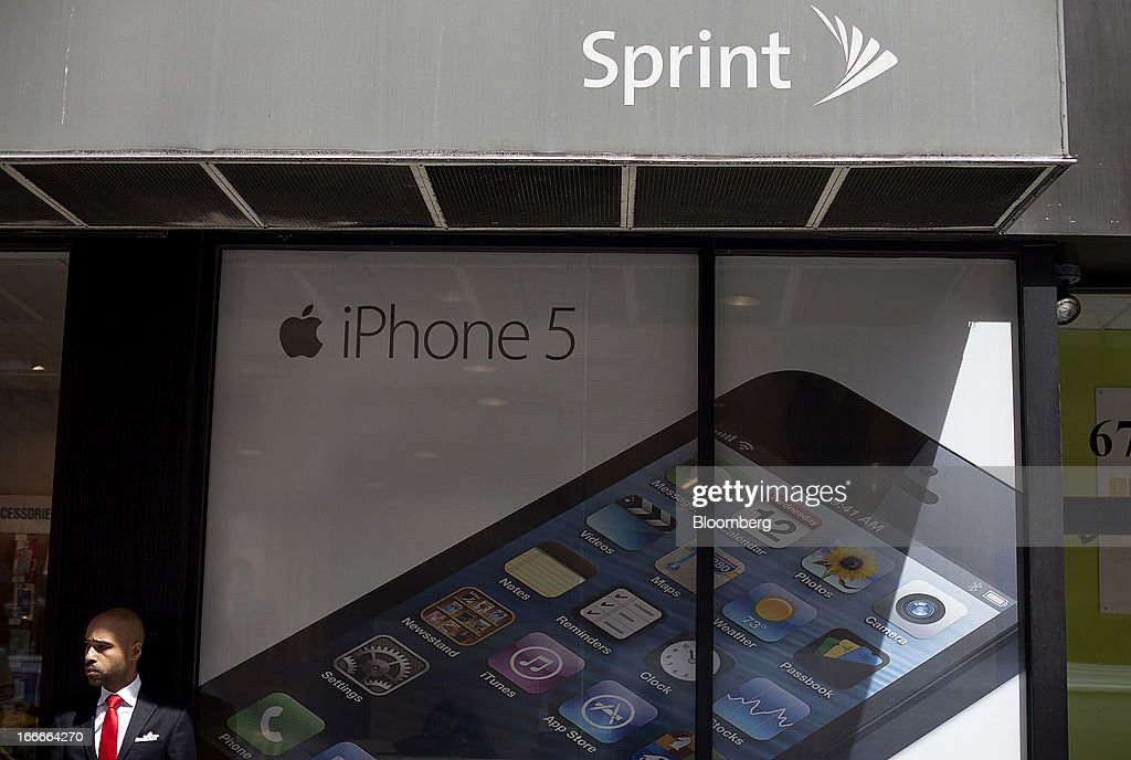 A man stands next to an Apple Inc. iPhone 5 advertisement displayed in the window of a Sprint Nextel Corp. store in New York, U.S., on Monday, April 15, 2013. Dish Network Corp., the satellite-TV company controlled by Charlie Ergen, made an unsolicited $25.5 billion offer for Sprint Nextel Corp., topping a Softbank Corp. bid for the third-largest U.S. wireless carrier. Photographer: Victor J. Blue/Bloomberg via Getty Images