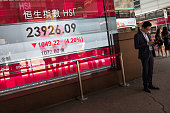 A man stands next to an electronic display showing the Hang Seng Index figure in Hong Kong China on Wednesday July 8 2015 Hong Kong's benchmark stock...
