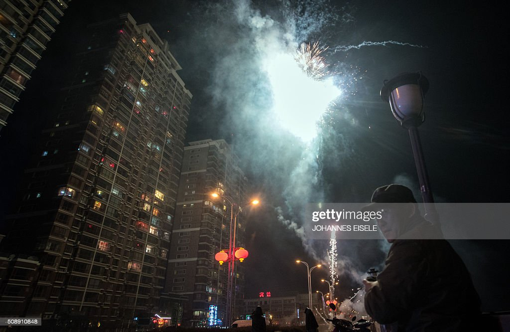A man stands next to fireworks celebrating the Lunar New Year near the Yalu River in the Chinese border town of Dandong opposite the North Korean town of Sinuiju on February 7, 2016. North Korea said on February 7, it had successfully put a satellite into orbit, with a rocket launch widely condemned as a ballistic missile test for a weapons delivery system to strike the US mainland. AFP PHOTO / JOHANNES EISELE / AFP / JOHANNES EISELE