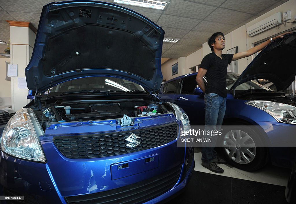 A man stands next to Suzuki cars on display at a show room in Yangon on February 6, 2013. Japanese automaker Suzuki said on February 6 it will resume production in Myanmar, the latest in a push by Asia's second-biggest economy to tap the once-isolated state. AFP PHOTO/ Soe Than WIN