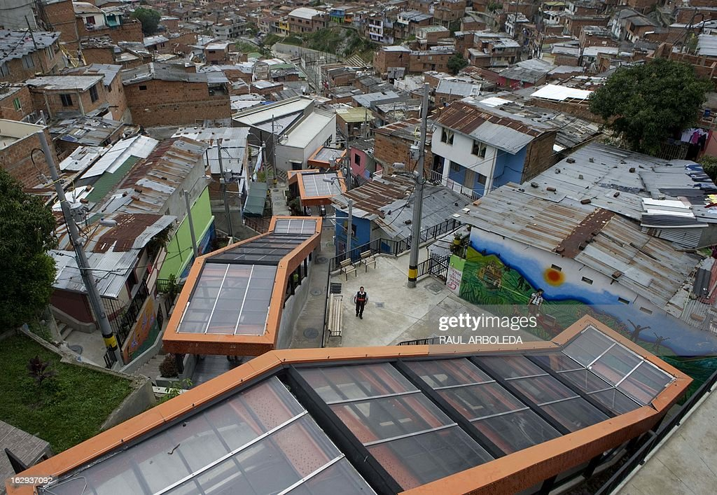 "A man (C) stands next to the covered escalators at Comuna 13 neighbourhood, one of the poorest and most violent areas of the northeastern Colombian city of Medellin, Antioquia department, Colombia on March 1, 2013. Medellin, which competed with New York and Tel Aviv, was chosen by popular vote through the internet, as the ""Innovative City of the Year"" during the City of the Year contest, organized by The Wall Street Journal and Citigroup. The distinction was basically made for its modern transportation system, its public library, escalators built in a shantytown and schools that have allowed the integration of society. AFP PHOTO/Raul ARBOLEDA"
