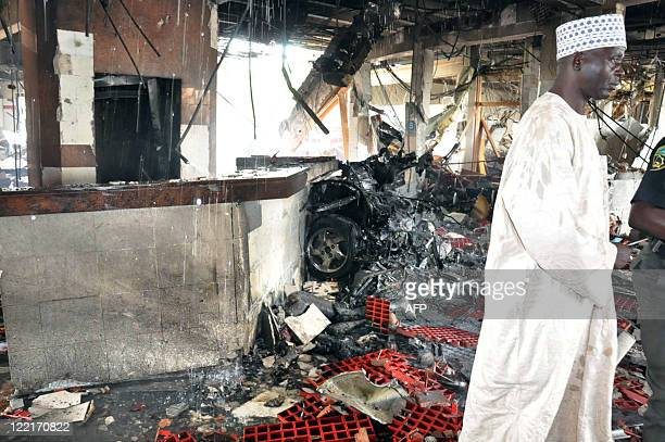 A man stands next to the debris of the car that rammed into building of the United Nations House in Abuja on August 26 2011 The suicide bomber...