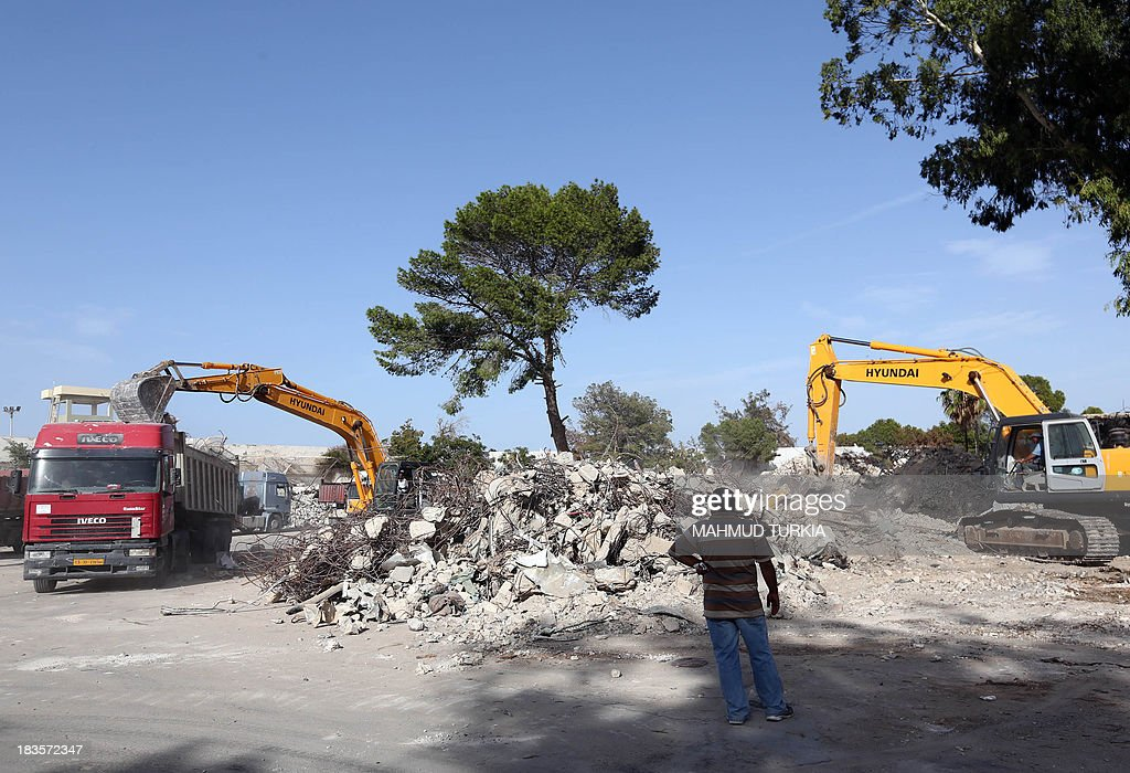 A man stands next to the rubble of former leader Moamer Kadhafi's Bab al-Azizia compound in Tripoli on October 7, 2013, which will be turned into a public recreation area for families, the Libyan Tourism Minister announced earlier this year. Bab al-Azizia 'The Splendid Gate' was a military barracks and compound, situated in the southern suburbs of the capital. It served as the main base for the Libyan leader Moamer Kadhafi until its capture by anti-Kadhafi forces on 23 August 2011, during the Battle of Tripoli. AFP PHOTO/MAHMUD TURKIA