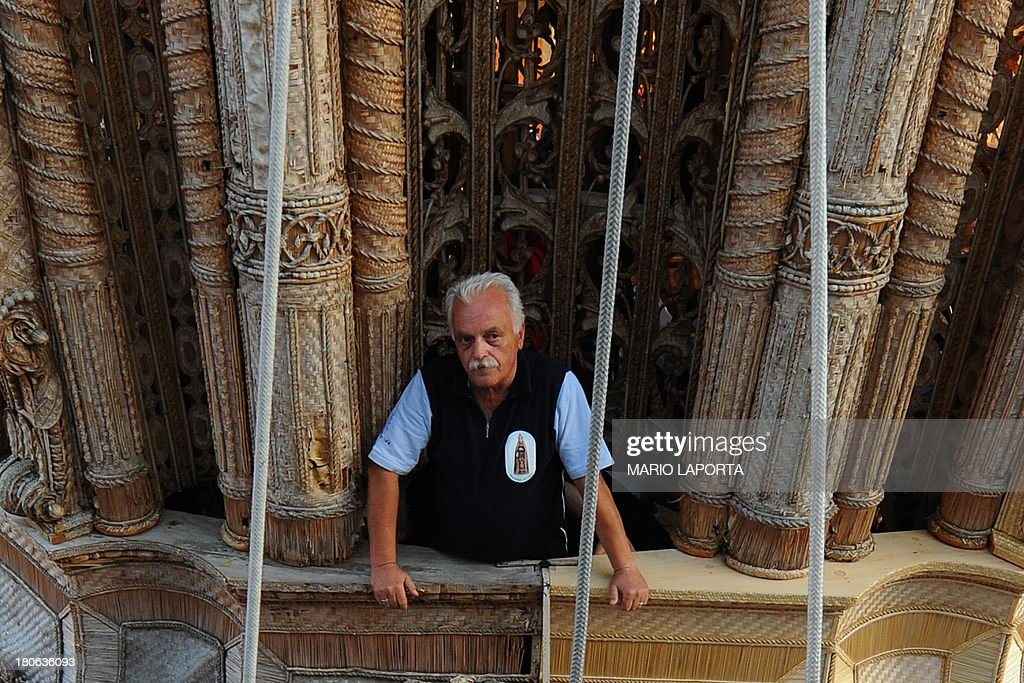 A man stands on a 25 meters wheat obelisk build in honor of Madonna Addolorata (Our Lady Of Sorrows) during a farmer festival in Mirabella Eclano, south of Italy on September 14, 2013. The ancient farmer festival (Medium Eve) after 900 years of stop, restart in XVI age to protect the hard work of farmers like religious festival in honour of the Lady Of Sorrows. 12 Oxen carry the obelisk and all the Mirabella Eclano citizens pull the ropes to balance the obelisk during the slow run.