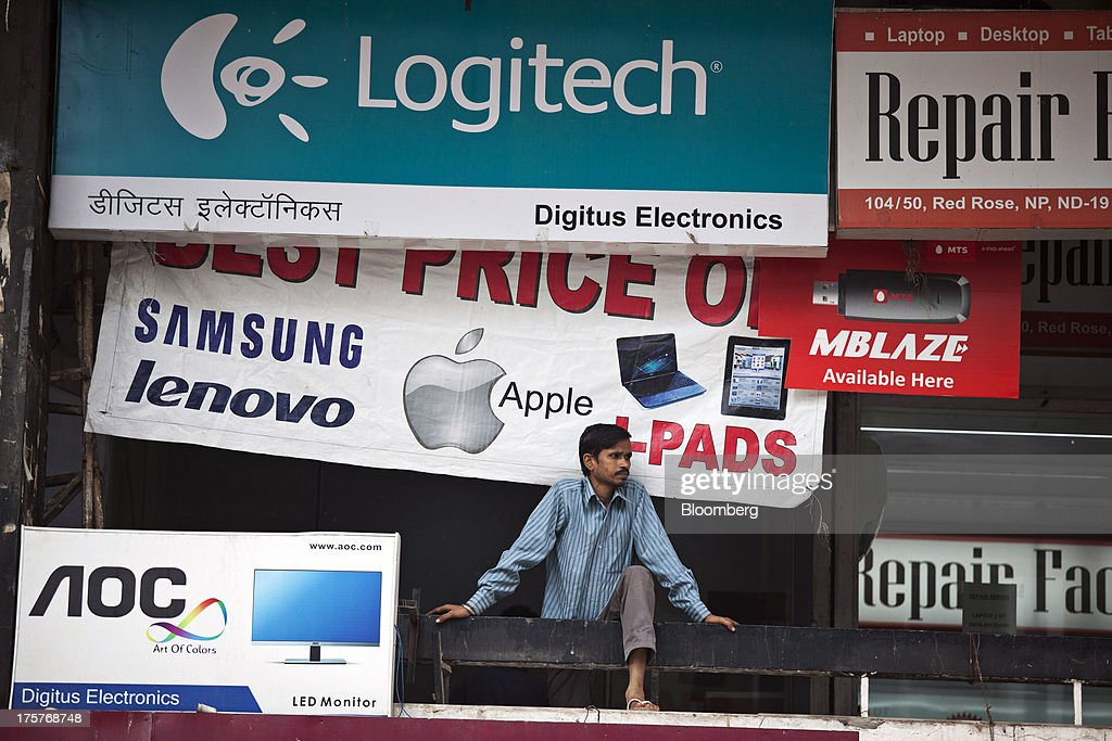A man stands on a balcony in front of advertisements for various companies in Nehru Place IT Market, a hub for the sale of electronic goods and computer accessories, in New Delhi, India, on Wednesday, Aug. 7, 2013. India's consumer price index (CPI) figures for July are scheduled to be released on August 12. Photographer: Graham Crouch/Bloomberg via Getty Images