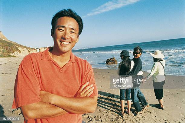 Man Stands on a Beach With his Arms Folded, Family in the Background Continue Walking