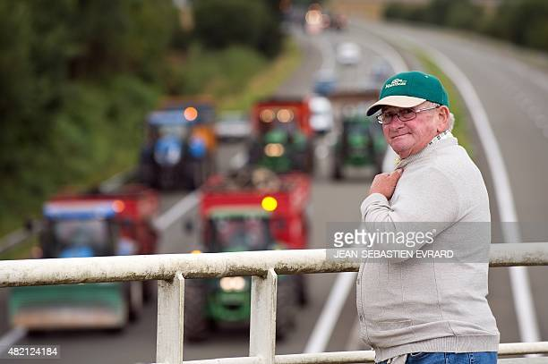 A man stands on a bridge as farmers below him block the A81 highway with tractors during a demonstration against the low sales prices of their...
