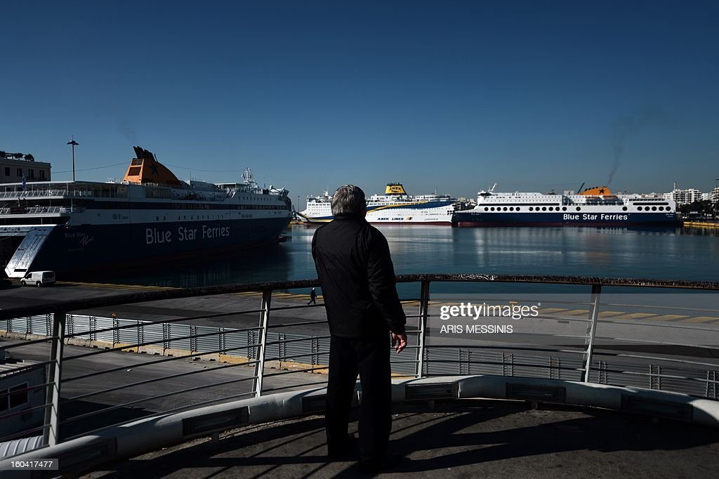 A man stands on a bridge opposite the port of Piraeus, near Athens, during a 48-hours strike on January 31, 2013. Sailors kicked off a two-day walkout, buses and trains were at a standstill and civil servants planned to hold a three-hour work stoppage against the government's cutbacks.