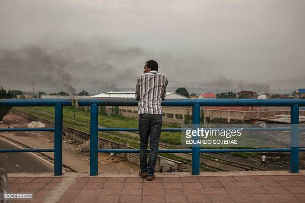 A man stands on a bridge while smoke from barricades rises in the sky on December 20 2016 in Kinshasa where tensions rose as the opposition leader...