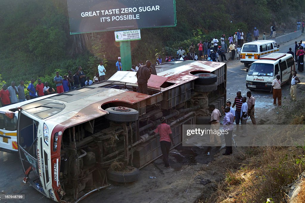 A man stands on a bus after it veered off the road and capsized as it with heading to the Moi international airport in Mombasa early on March 2, 2013. Six of the 15 tourists on board were injured and taken to the hospital. AFP PHOTO / STR