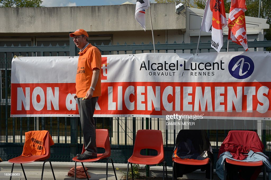 A man stands on a chair by a banner reading 'No to layoffs' during a protest on October 8, 2013 in Orvault, western France, in front of the plant of French-US telecom-equipment maker Alcatel-Lucent, after the group announced the cut of 10,000 jobs worldwide to reduce fixed costs by 15 percent in two years. The company said that 4,100 jobs would be cut in Europe, the Middle East and Africa by 2015, 3,800 in the Asia Pacific region, and 2,100 in North and South America. AFP PHOTO DAMIEN MEYER