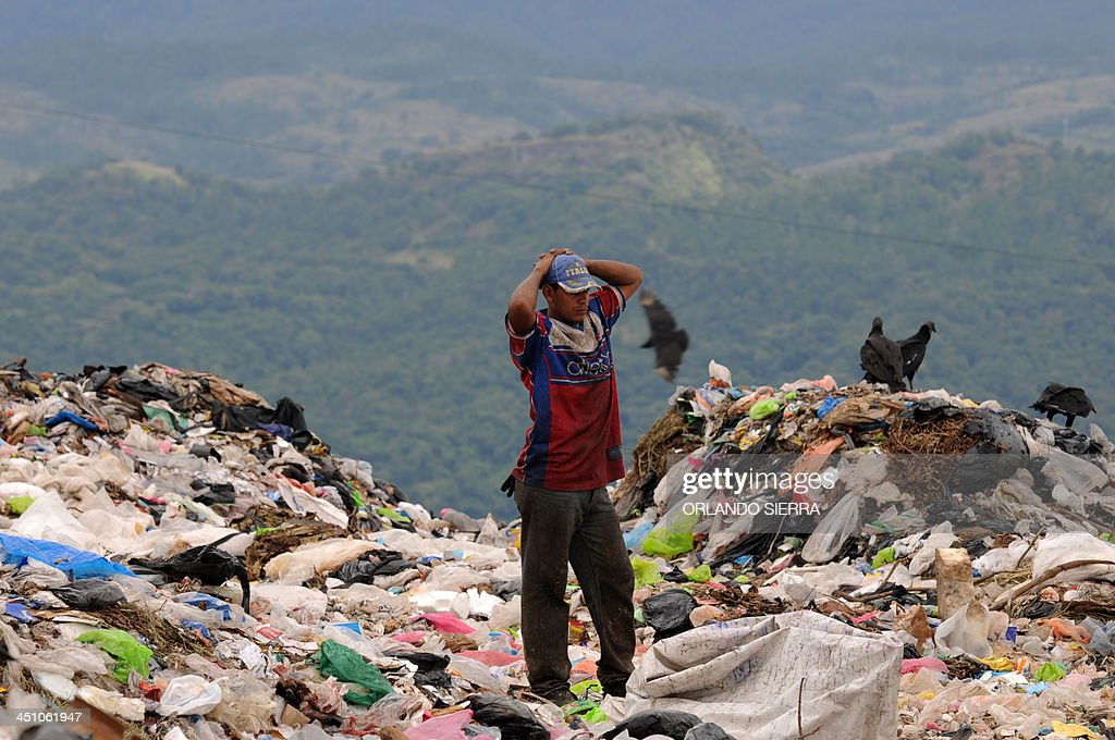A man stands on a heap of garbage at the municipal rubbish dump 20 km north of Tegucigalpa on November 21 2013 Honduras one of the poorest Latin...