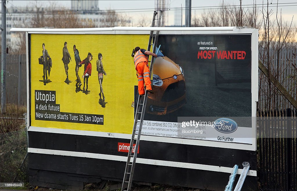 A man stands on a ladder and pastes over an advertisement for Ford Motor Co. automobiles on a Primesight billboard in London, U.K., on Thursday, Jan. 3 2013. U.K. services unexpectedly shrank for the first time in two years in December, clouding the economic outlook as Britain struggles to avoid a triple-dip recession. Photographer: Chris Ratcliffe/Bloomberg via Getty Images
