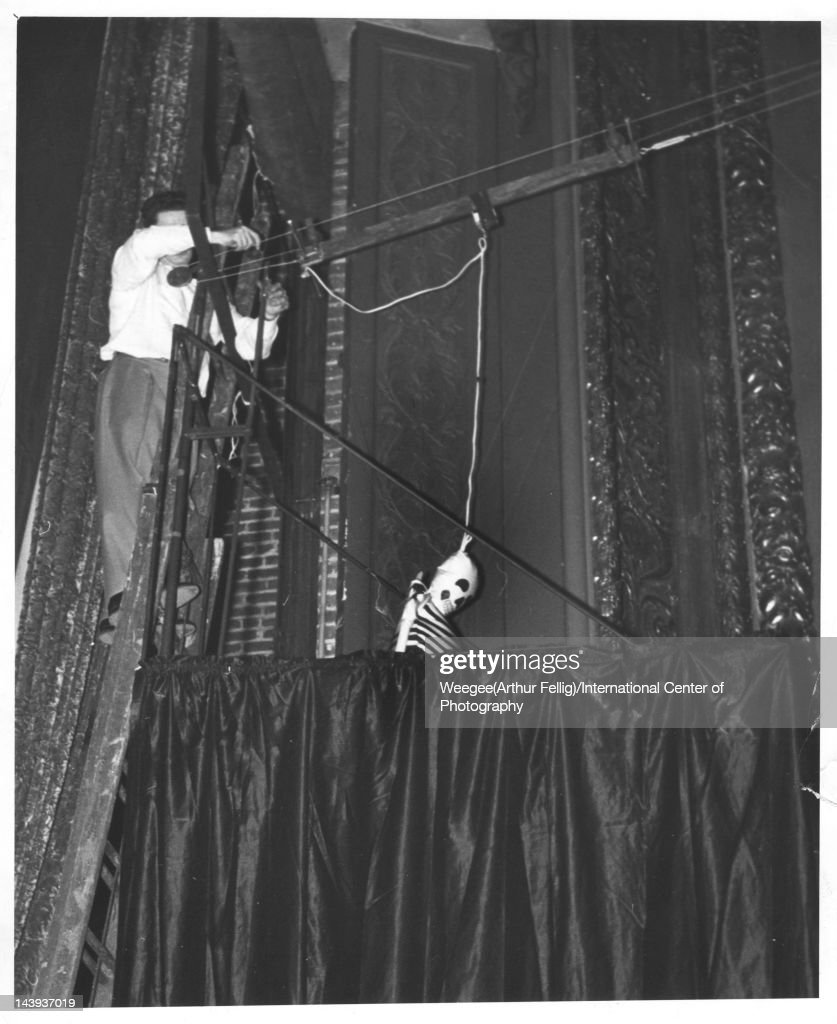 A man stands on a ladder as he prepares to swing an inflatable skeleton over a movie theatre audience late 1950s or early 1960s During screenings of...