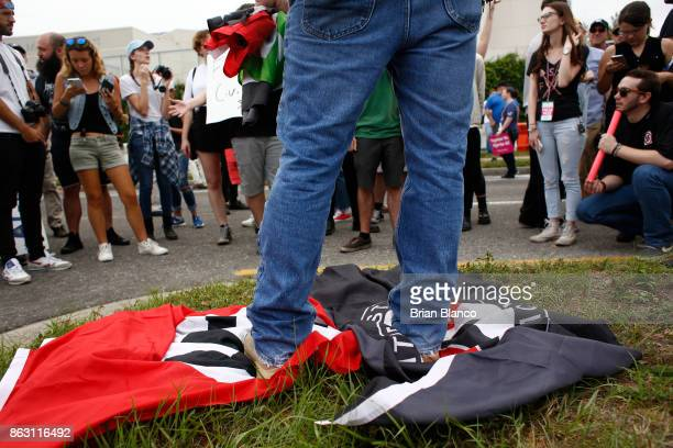 A man stands on a Nazi flag and an ANTIFA flag as demonstrators gather near the site of a planned speech by white nationalist Richard Spencer who...
