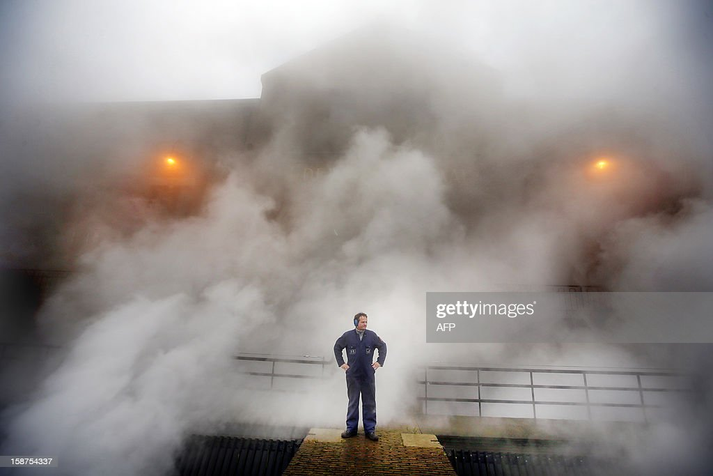 A man stands on a platform as steam rises from the boilers of a pumping-station in Lemmer, the northern Netherlands, on December 24, 2012. The station pumps excess water from the northern province to a nearby lake. The authorities decided to turn on the pumping-station due to expected heavy rainfall. AFP PHOTO / ANP / CATRINUS VAN DER VEEN