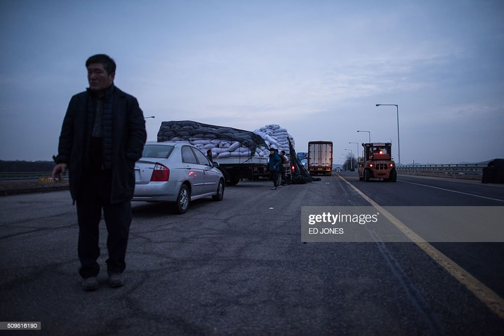 A man stands on a roadside before vehicles, which arrived from the Kaesong joint industrial zone, outside a checkpoint near the Demilitarized Zone (DMZ) separating the two Koreas in Paju on February 11, 2016. North Korea on February 11 expelled all South Koreans from the jointly-run Kaesong industrial zone and seized their factory assets, saying Seoul's earlier decision to shutter the complex had amounted to a 'declaration of war'. AFP PHOTO / Ed Jones / AFP / ED JONES