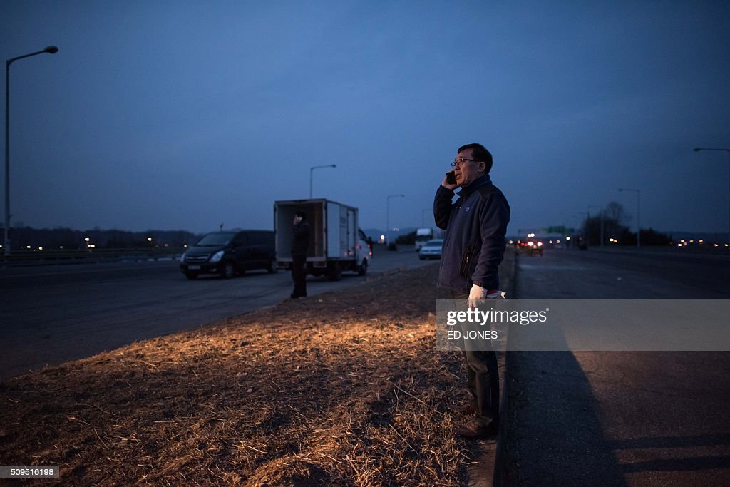 A man stands on a roadside before vehicles, which arrived from the Kaesong joint industrial area, being offloaded outside a checkpoint near the Demilitarized Zone (DMZ) separating the two Koreas in Paju on February 11, 2016. North Korea on February 11 expelled all South Koreans from the jointly-run Kaesong industrial zone and seized their factory assets, saying Seoul's earlier decision to shutter the complex had amounted to a 'declaration of war'. AFP PHOTO / Ed Jones / AFP / ED JONES