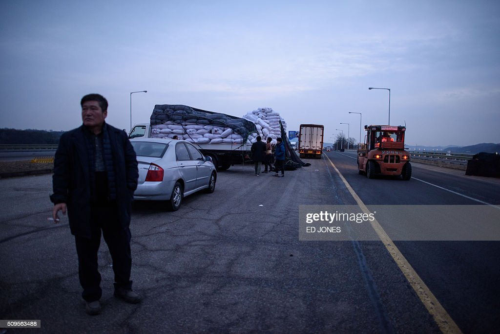 A man stands on a roadside before vehicles which arrived from the Kaesong joint industrial zone, outside a checkpoint near the Demilitarized Zone (DMZ) separating North and South Korea, in Paju on February 11, 2016. North Korea on February 11 expelled all South Koreans from the jointly-run Kaesong industrial zone and seized their factory assets, saying Seoul's earlier decision to shutter the complex had amounted to a 'declaration of war'. AFP PHOTO / Ed Jones / AFP / ED JONES
