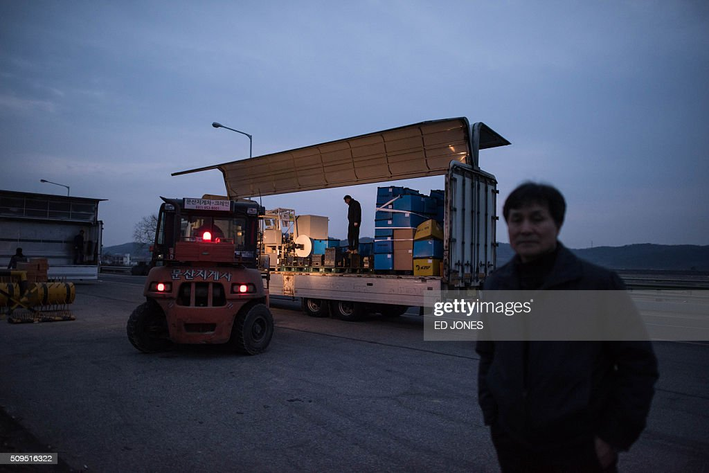 A man stands on a roadside by vehicles carrying machines for manufacturing car parts, after arriving from the Kaesong joint industrial area, outside a checkpoint near the Demilitarized Zone (DMZ) separating the two Koreas in Paju on February 11, 2016. North Korea on February 11 expelled all South Koreans from the jointly-run Kaesong industrial zone and seized their factory assets, saying Seoul's earlier decision to shutter the complex had amounted to a 'declaration of war'. AFP PHOTO / Ed Jones / AFP / ED JONES