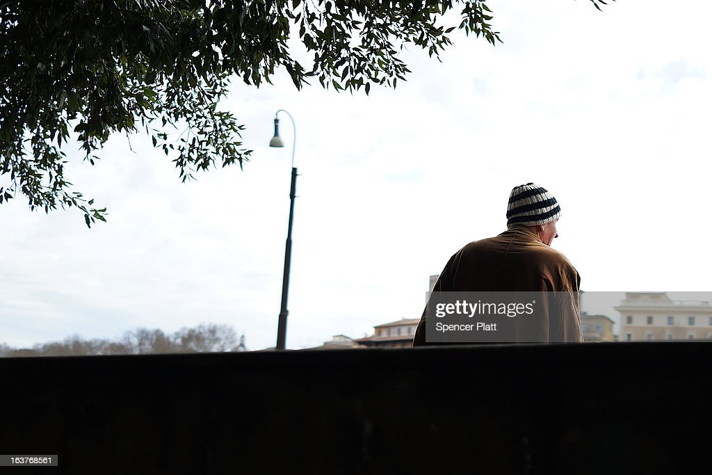 A man stands on a street corner next to a group of homeless men along the Tiber River on March 15, 2013 in Rome, Italy. Newly elected Pope Francis, formerly Cardinal Jorge Mario Bergoglio of Buenos Aires, has been a strong advocate for the poor and disenfranchised throughout the world. A Jesuit, Francis has followed the tradition of his order whose members live spartan, communal lives of poverty. Many analysts believe his papacy will see increased outreach and advocacy for the poor.