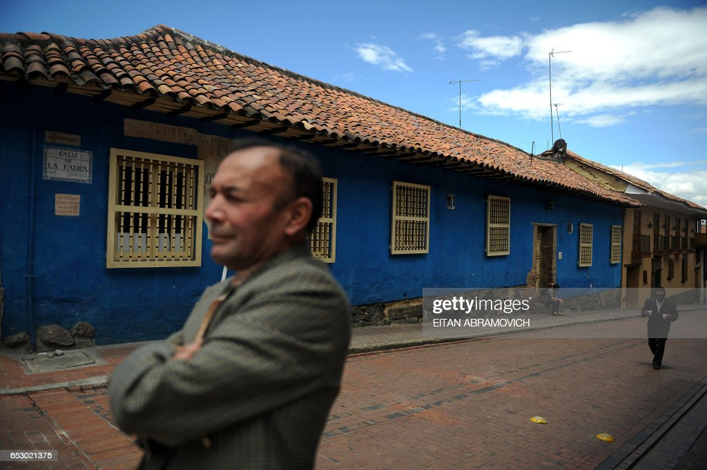 A man stands on a street corner while another brings two cups of coffee in the historic neighborhood of La Candelaria in Bogota on September 17, 2009. La Candelaria is Bogota's oldest neighbourhood and the city's historical center, known for its colonial houses with wooden balconies and clay shingle roofs. AFP PHOTO/Eitan Abramovich /
