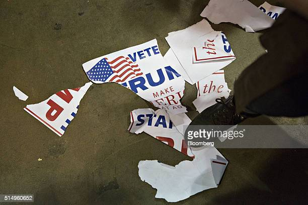 A man stands on a torn campaign sign during a canceled campaign event with Donald Trump president and chief executive of Trump Organization Inc and...