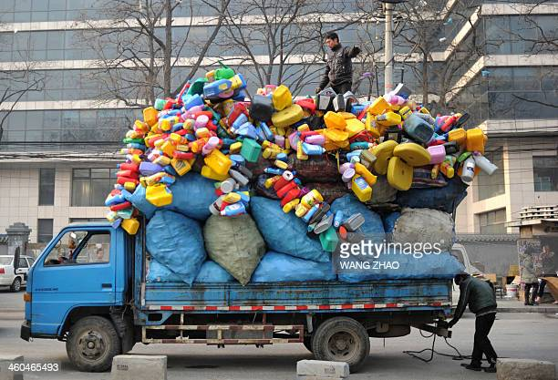 A man stands on a truck full of recycled goods parks on a road in Beijing on January 4 2014 Chinese manufacturing grew at its slowest pace in three...