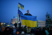 A man stands on a wall holding a Ukrainian flag while listening to speakers on stage in Independence Square on February 26 2014 in Kiev Ukraine...