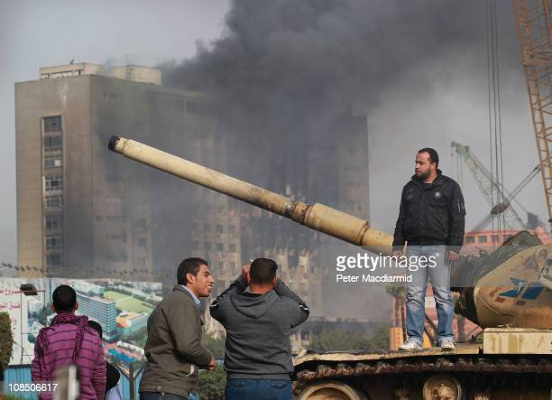A man stands on an army tank in Tahrir Square as the headquarters of the ruling National Democratic Party continue to burn on January 29 2011 in...