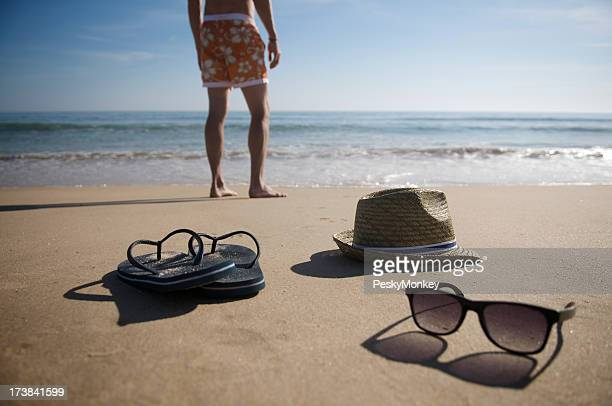 Man Stands on Beach Sunglasses Flipflops Hat and Surf Shorts